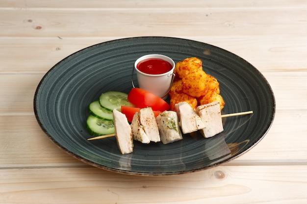 Кусочки куриного филе на шпажке с жареными картофельными шариками и овощами