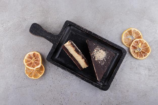 말린 레몬 조각과 초콜릿 케이크 조각을 돌 테이블에 배치합니다.