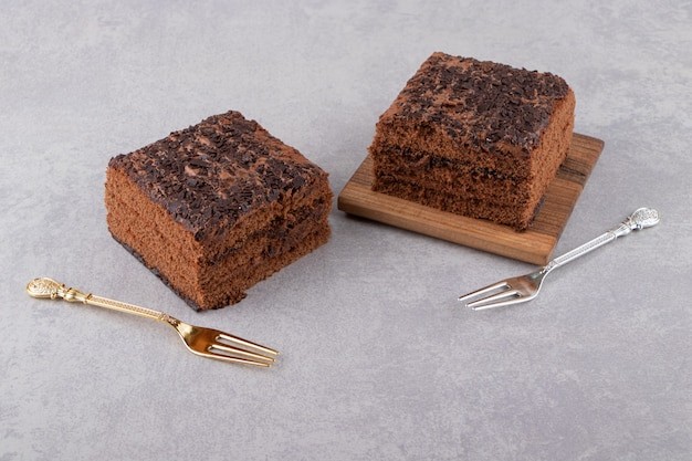 포크와 초콜릿 케이크 조각을 돌 테이블에 배치합니다.