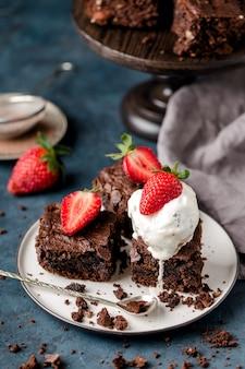 초콜릿 너트 브라우니 조각, 아이스크림 한 스쿱, 하얀 접시, 숟가락, 딸기 조각, 부스러기, 회색 직물. 진한 파란색 배경입니다. 수직의