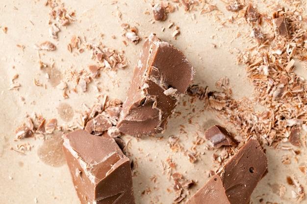 テーブルの上にランダムに散らばったチョコレートのかけら、壊れて砕けた天然チョコレート、カカオと砂糖から作られた食用ミルクチョコレート
