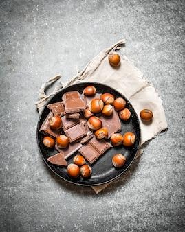 Кусочки шоколада с орехами на старой тарелке. на черном деревянном столе.