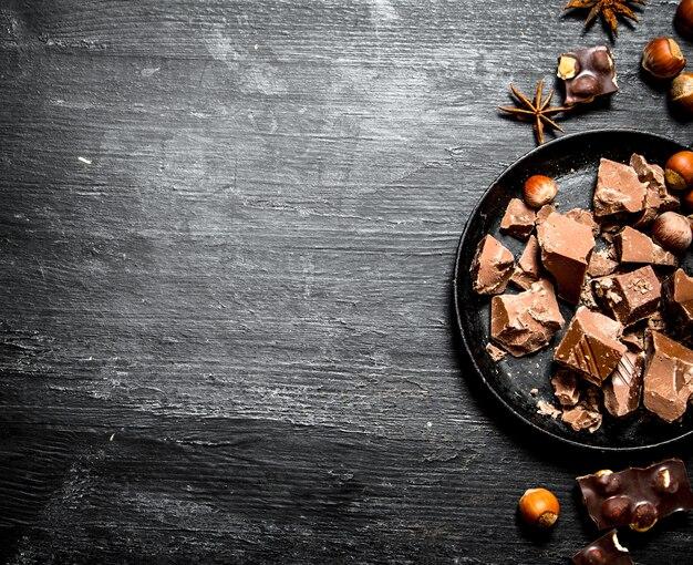 ナッツ全体が入ったチョコレートのかけら。黒い木製の背景に。