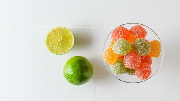 ガラスのボウルにカラフルなマーマレードと白いテーブルにライムの作品。砂糖とゼリーを使った美味しいお菓子。上からの眺め。