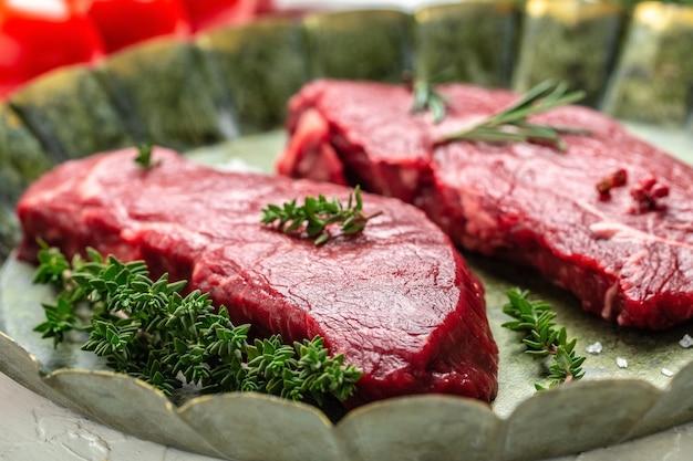 Кусочки жареного стейка из круп со специями подаются на старом мясном подносе. стейк из мраморной говядины блэк ангус. стейк из сырой говядины, вид сверху.