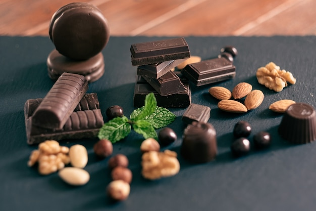 ミントの葉と黒の背景にダークチョコレートとドライフルーツのかけら。木製のテーブル