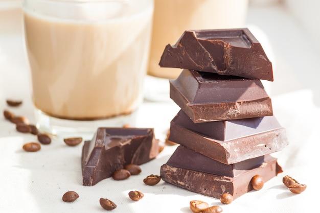 ダークチョコレート、コーヒービーンズ、ココアまたはコーヒーと牛乳のカップ。