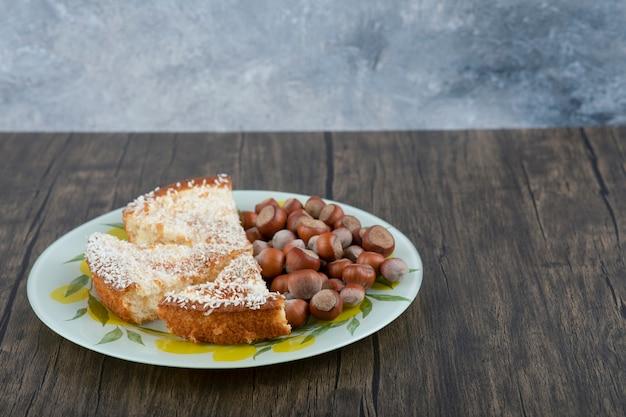 마카다미아 너트와 함께 맛있는 케이크 조각을 나무 테이블에 배치