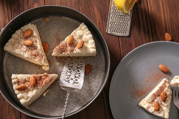 베이킹 접시에 아몬드와 함께 맛있는 치즈 케이크 조각