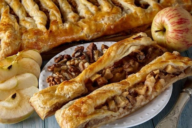 白い皿にリンゴとナッツ、リンゴとナッツが入ったおいしい自家製パイのかけら。パイと材料