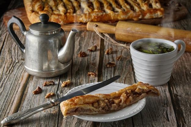 白い皿にリンゴとナッツを添えたおいしい自家製パイのかけら