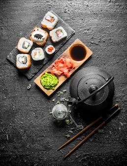 Кусочки вкусных японских суши-роллов с зеленым чаем и соусами. на черном деревенском столе