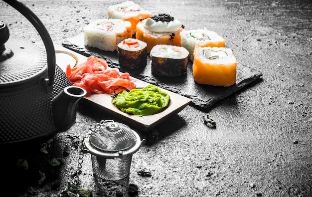 Кусочки вкусных японских суши-роллов с зеленым чаем и соусами.