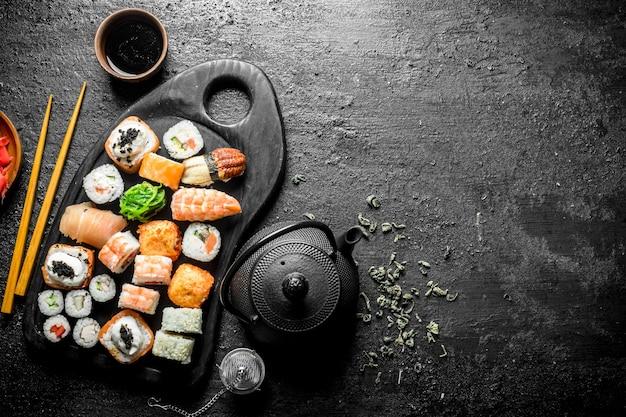 Кусочки вкусных суши-роллов на разделочной доске с чаем в чайнике на деревенском столе