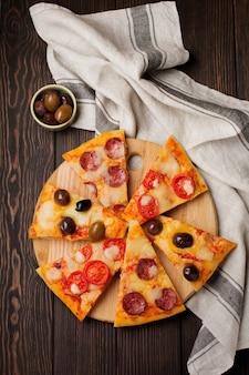 ダークウッドの素朴な上にオリーブ、イタリアンマルガリータ、ペパロニを添えたさまざまなギリシャのピザのピース。