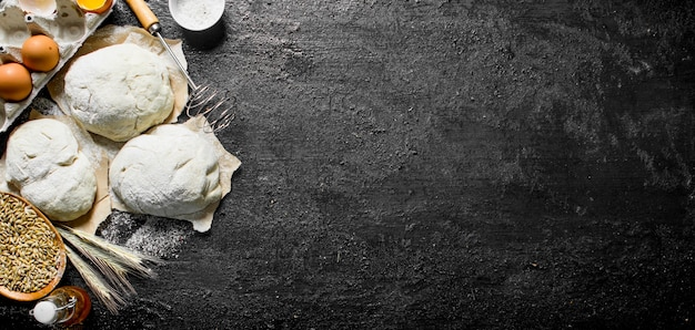 黒い素朴なテーブルのボウルに泡立て器、卵、穀物の生地の断片