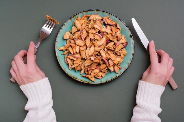 緑の背景に女性の手で皿とカトラリーに乾いたリンゴの断片。健康的な食事