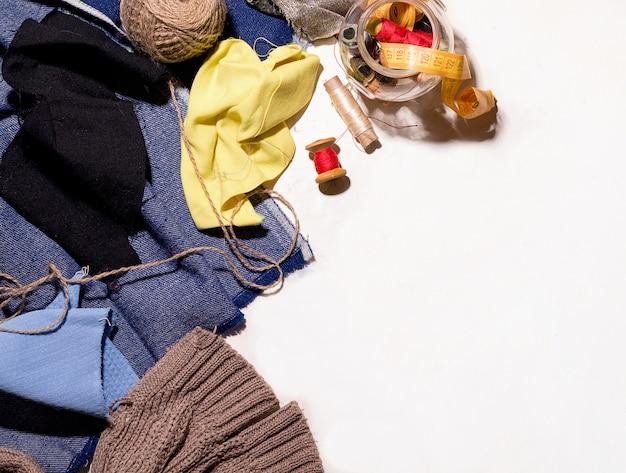 スレッドと白いテーブルのボタンの横にある異なる色の生地の部分。ボロ縫製コンセプト