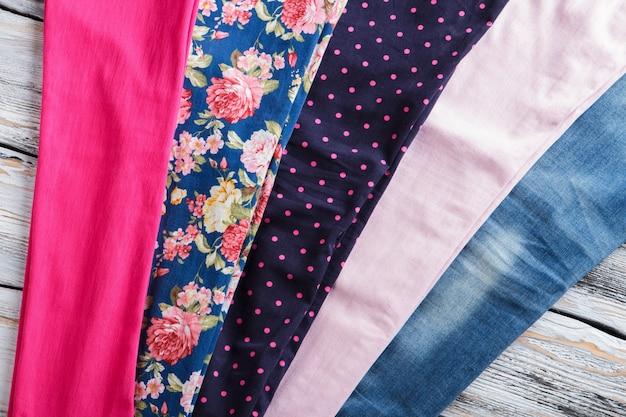 패턴이 있는 천 조각. 흰색 나무 배경에 천입니다. 분홍색 점과 붉은 꽃. 옷 작업장의 테이블입니다.
