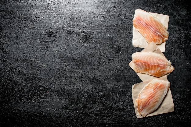 紙ナプキンに魚の切り身のかけら。黒の素朴な背景に