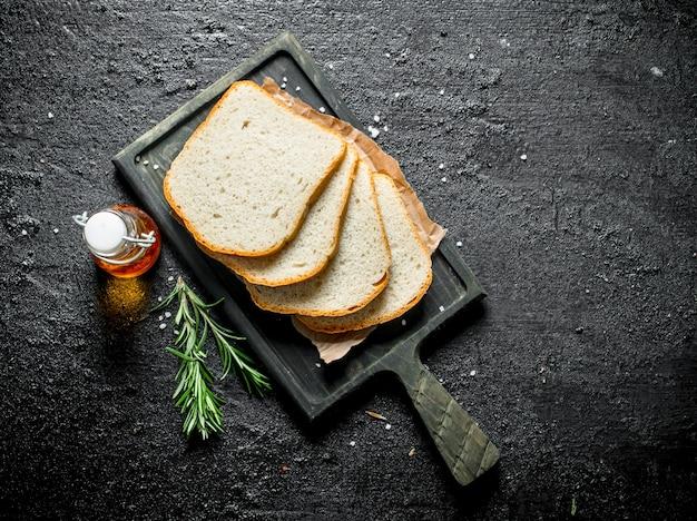 Кусочки свежего хлеба с розмарином. на черном деревенском фоне