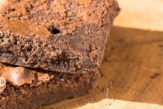 Кусочки свежего домового на деревянных фоне. вкусный шоколадный пирог. макро крупным планом. выборочный фокус. Premium Фотографии