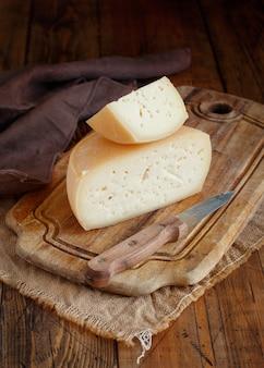 Кусочки свежего домашнего сыра на деревянной доске крупным планом