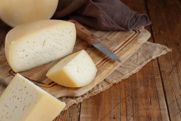 木の板の上面図に新鮮な自家製チーズのかけら