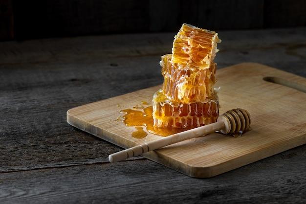 Кусочки свежих сот с медом и деревянной палочкой