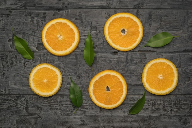 新鮮なオレンジのかけらと黒い木製のテーブルの葉。フラットレイ。