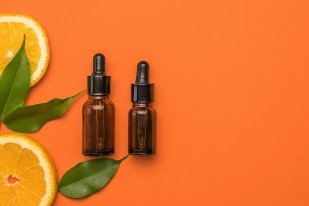 Кусочки свежих апельсинов, листьев и медицинских бутылок на оранжевом фоне.
