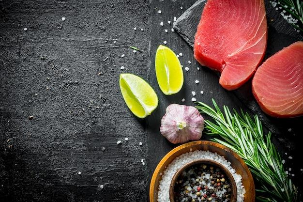 Кусочки свежего сырого тунца на каменной доске со специями, чесноком, лаймом и розмарином. на черном деревенском фоне