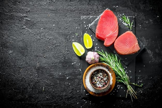 Кусочки свежего сырого тунца на каменной доске со специями, чесноком, лаймом и розмарином на черном деревенском столе.