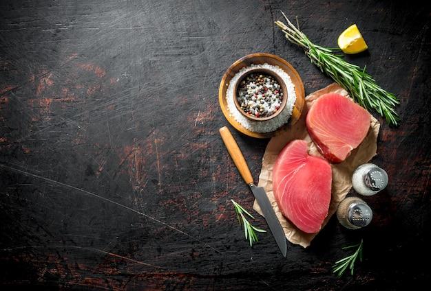 Кусочки свежего сырого тунца на бумаге со специями, розмарином и долькой лимона на темном деревенском столе.