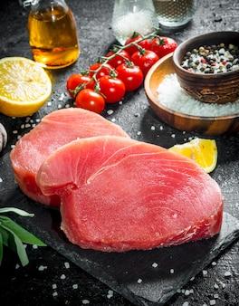 Кусочки свежего сырого тунца с помидорами, специями и лимоном. на черной деревенской поверхности
