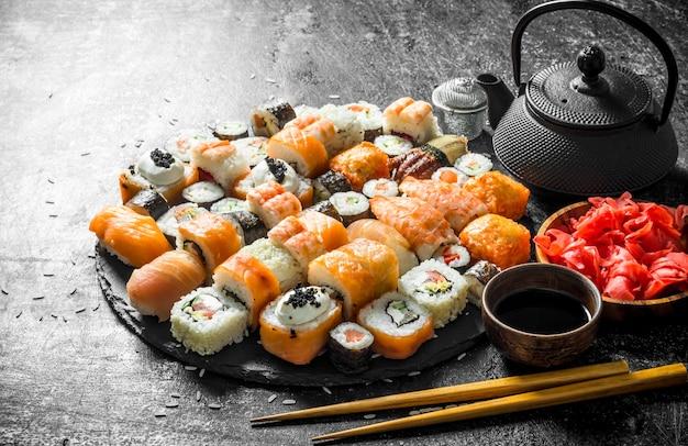 Кусочки свежих суши-роллов на каменной подставке с чаем, соевым соусом и палочками для еды. на темном деревенском фоне
