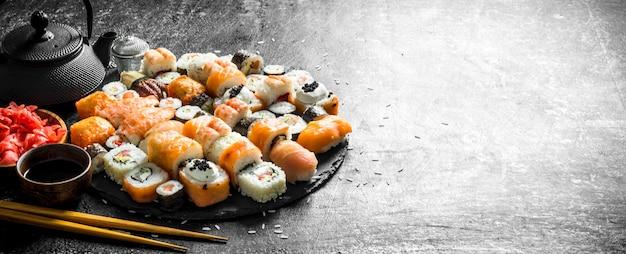 Кусочки свежих суши-роллов на каменной подставке с чаем, соевым соусом и палочками для еды. на темной деревенской поверхности