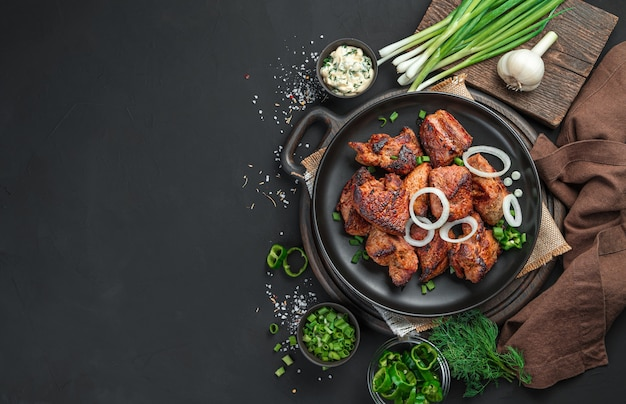 검은 접시에 신선한 양파와 함께 튀긴 고기 조각. 케밥, 검은 배경에 바베큐. 평면도.