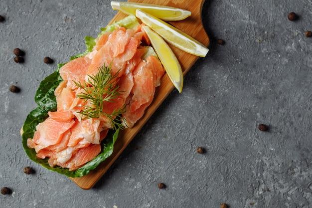 Кусочки жареного лосося с укропом и дольками лимона на деревянной доске