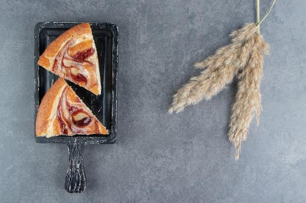 暗いまな板の上のフルーツケーキの断片