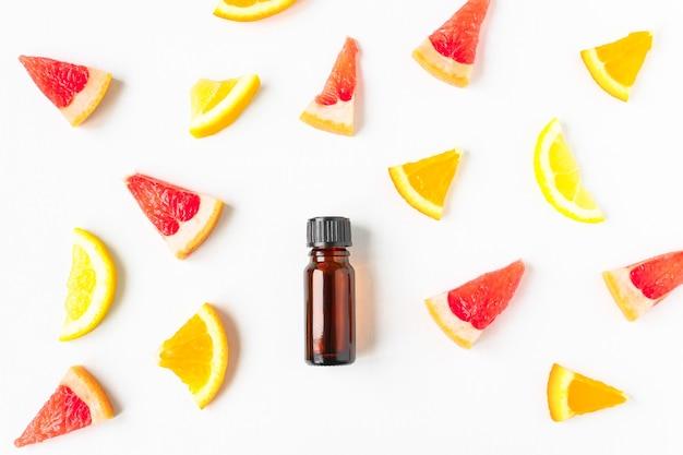 호박색 병에 에센셜 오일을 넣은 흰색 나무 배경에 있는 과일 조각