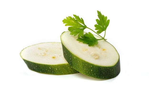 흰색 배경에 파슬리와 함께 녹색 줄무늬 호박 조각.