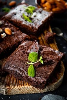 Кусочки домашнего шоколадного брауни, украшенные листьями мяты, крупным планом вертикальное фото. фото высокого качества