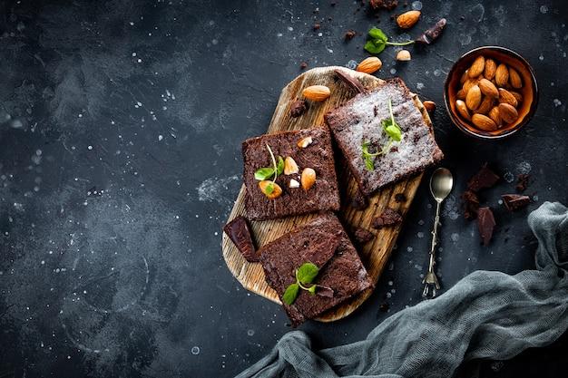 Кусочки домашнего шоколадного пирожного с листьями мяты и орехами на сером фоне, copyspace вид сверху. фото высокого качества