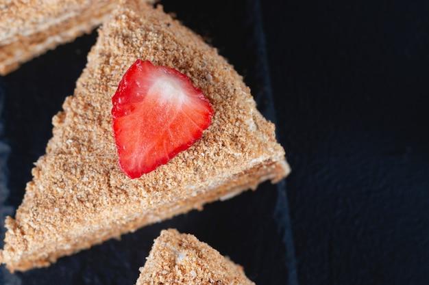 어두운 배경에 딸기와 꿀 케이크의 조각