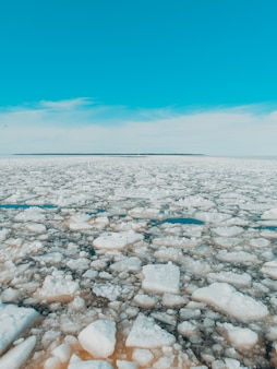 冬の明るい空の下で凍った湖の氷