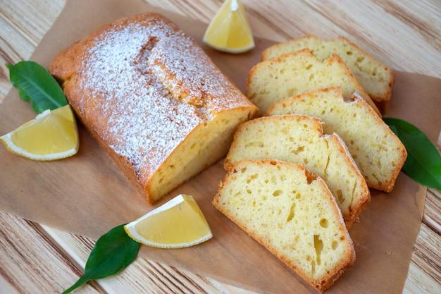 素朴な木の板にフルパイレモンとレモンケーキのかけら。