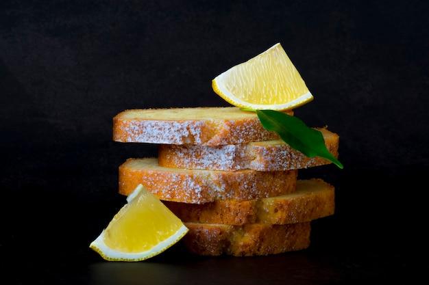 Кусочки лимонного торта с сахарной пудрой и ломтиками лимона на темном фоне.