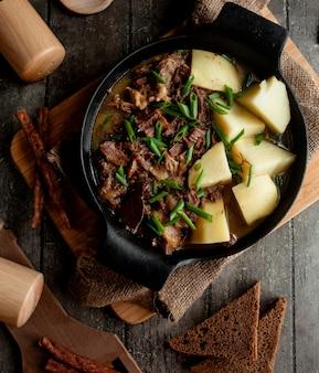 Кусочки мяса и картофеля, приготовленные в алюминиевой посуде
