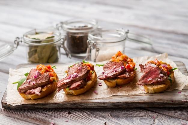 토스트에 고기 조각입니다. 다진 야채의 혼합물. 송아지 고기를 곁들인 브루스케타 레시피. 간편하게 조리할 수 있는 식사.